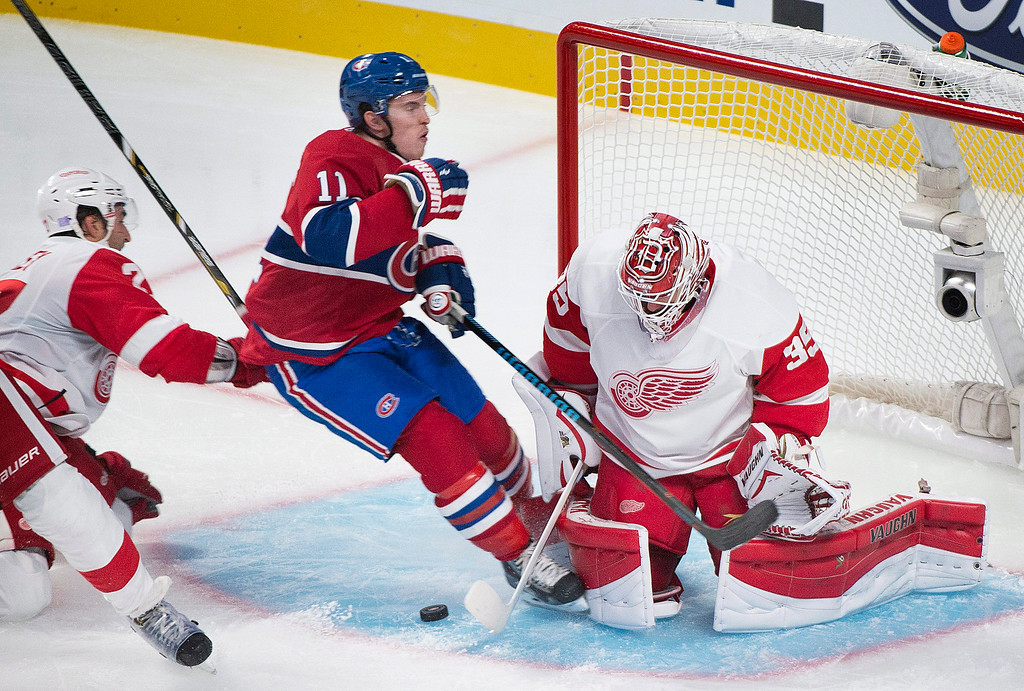 . Montreal Canadiens\' Brendan Gallagher, center slides in on Detroit Red Wings goaltender Jimmy Howard as Red Wing\'s Kyle Quincey, left, defends during second period NHL hockey action in Montreal, Tuesday, Oct. 21, 2014. (AP Photo/The Canadian Press, Graham Hughes)