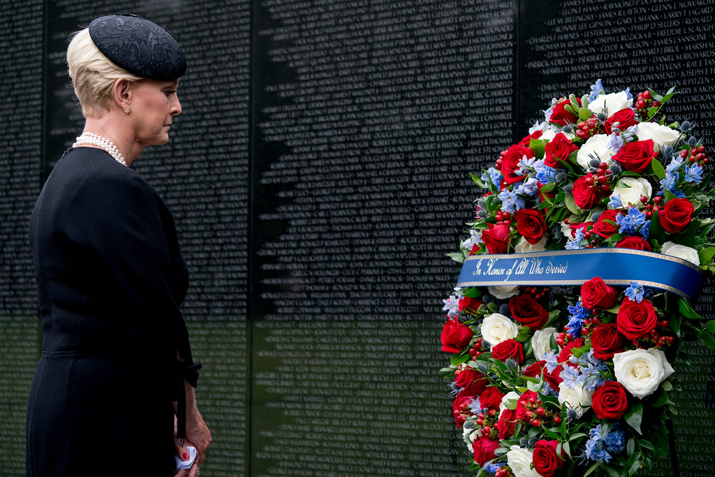 . Cindy McCain, wife of, Sen. John McCain, R-Ariz., lays a wreath at the Vietnam Veterans Memorial in Washington, Saturday, Sept. 1, 2018, during a funeral procession to carry the casket of her husband from the U.S. Capitol to National Cathedral for a Memorial Service. McCain served as a Navy pilot during the Vietnam War and was a prisoner of war for more than five years. (AP Photo/Andrew Harnik, Pool)