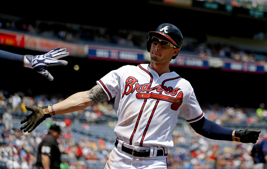 . Atlanta\'s Jordan Schafer high-fives teammate Freddie Freeman after scoring off a single by Jason Heyward in the first inning. (AP Photo/David Goldman)