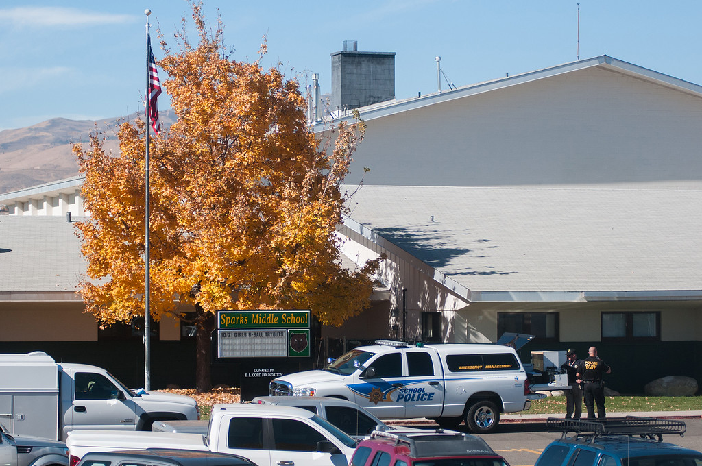 . Police are staged in front of Sparks Middle School after a shooting in Sparks, Nev. on Monday, Oct. 21, 2013 in Sparks, Nev.  (AP Photo/Kevin Clifford)