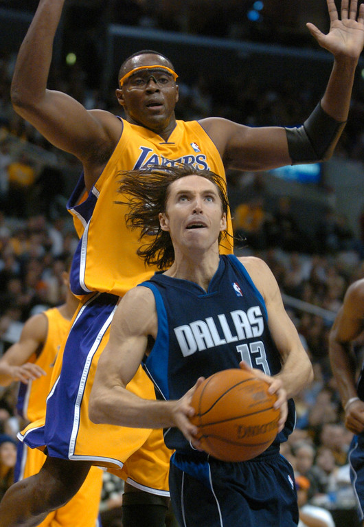 . Dallas Mavericks\' Steve Nash, bottom, escapes the pressure of Los Angeles Lakers\' Horace Grant during the first half at Staples Center in Los Angeles, Friday, Dec. 12, 2003. (AP Photo/Chris Pizzello)