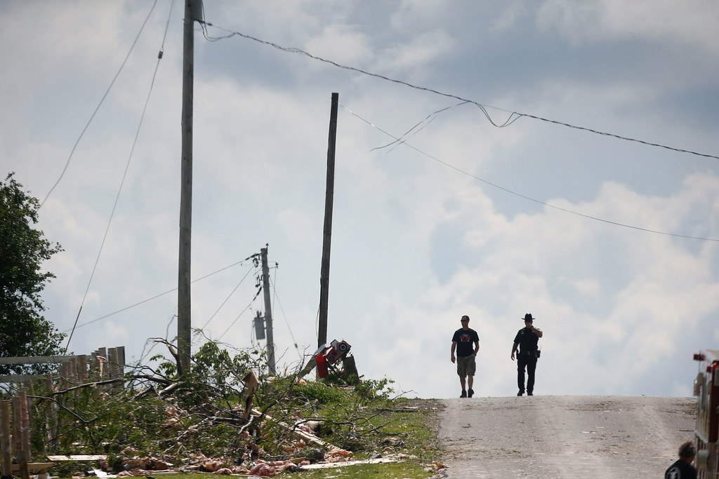 . Debris is seen along a road after Tuesday\'s storm, on Wednesday, July 9, 2014, in Smithfield, N.Y. (AP Photo/Mike Groll)