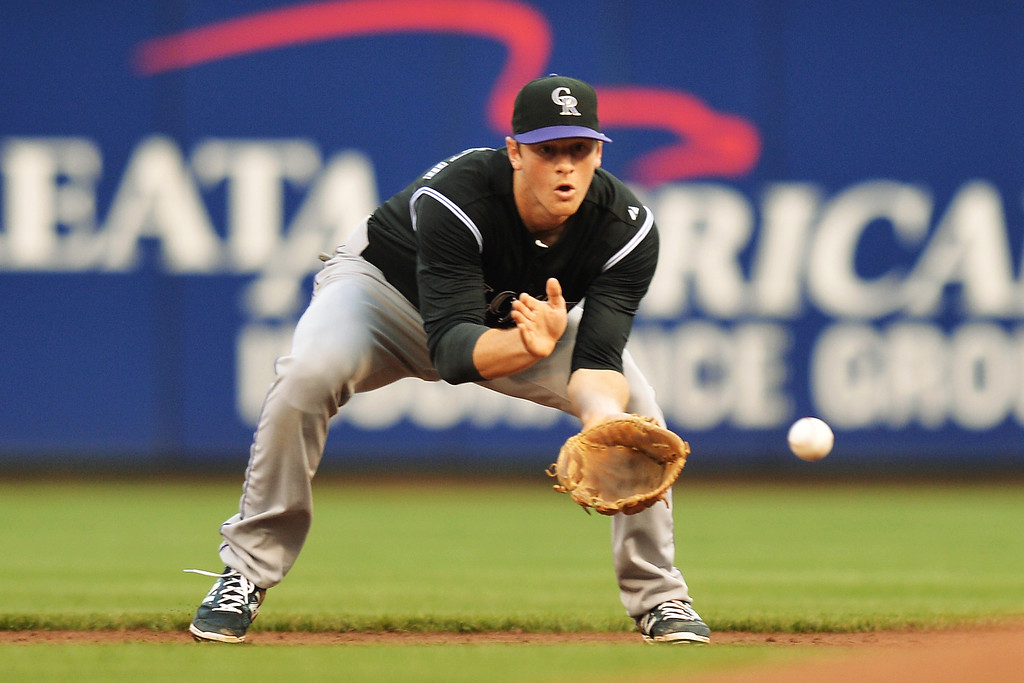 . CINCINNATI, OH - MAY 10:  DJ LeMahieu #9 of the Colorado Rockies fields a ground ball in the second inning against the Cincinnati Reds at Great American Ball Park on May 10, 2014 in Cincinnati, Ohio.  (Photo by Jamie Sabau/Getty Images)