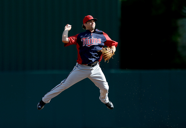 Description of . Minnesota Twins' Brian Dozier jumps in the air as he fields a ball to throw to first base during a spring training baseball workout, Friday, Feb. 22, 2013, Fort Myers, Fla. (AP Photo/David Goldman)