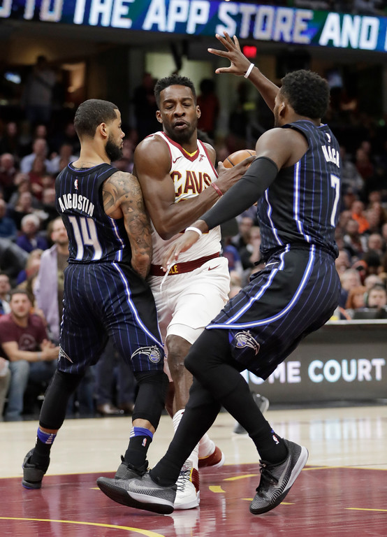 . Cleveland Cavaliers\' Jeff Green (32) drives between Orlando Magic\'s D.J. Augustin (14) and Shelvin Mack (7) in the first half of an NBA basketball game, Thursday, Jan. 18, 2018, in Cleveland. (AP Photo/Tony Dejak)