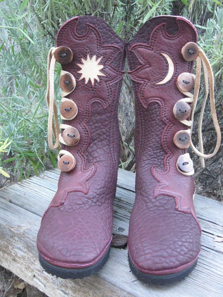 Redwood buffalo five button moccasins, with redwood bullhide lotus flower button trim, inset of moon and sun in palomino deerskin, sand heel and laces, redwood tabs, medium antler sidecut buttons.  Note that the boots are cut in the shape of the full welt without the deerskin added.