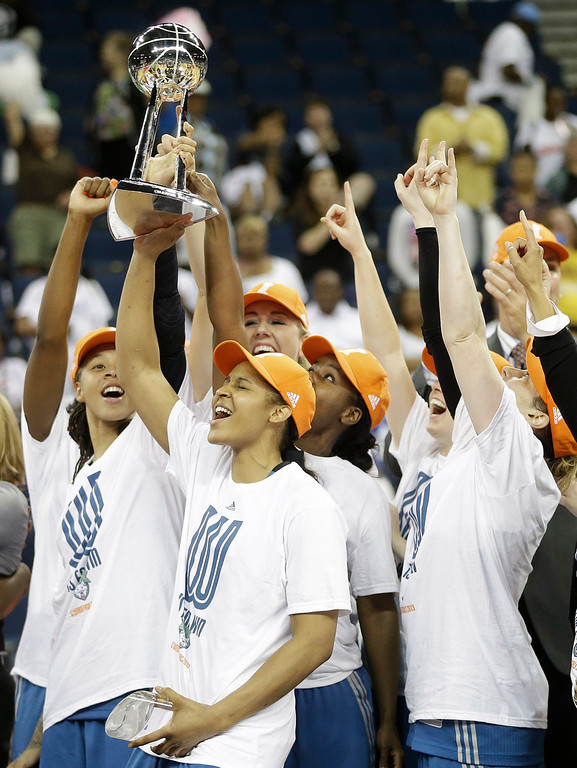 . Minnesota Lynx\' Maya Moore, second from left, holds the championship trophy with teammates after the second half of Game 3 of the WNBA Finals basketball series against the Atlanta Dream, in Duluth, Ga., Thursday, Oct. 10, 2013. The Minnesota Lynx won 86- 77. (AP Photo/John Bazemore)