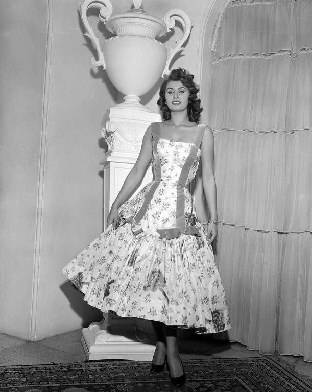 . Italian actress Sophia Loren wears a cocktail dress of cyclamen printed taffetta with an H-line treatment of lilac ribbon ending in bows above a deep flounce, designed by Emilio Schuberth of Rome, Jan. 24, 1955, in Rome.  (AP Photo)
