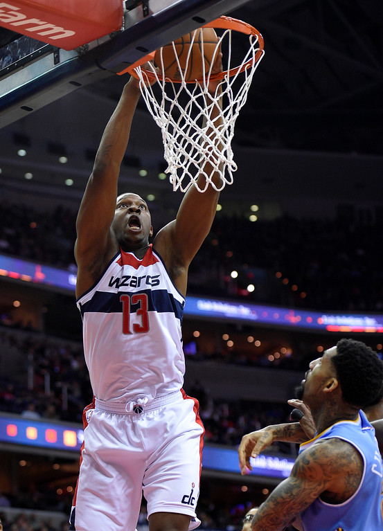 . Washington Wizards center Kevin Seraphin (13), of France, dunks over Denver Nuggets forward Wilson Chandler, right, during the second half of an NBA basketball game, Friday, Dec. 5, 2014, in Washington. (AP Photo/Nick Wass)