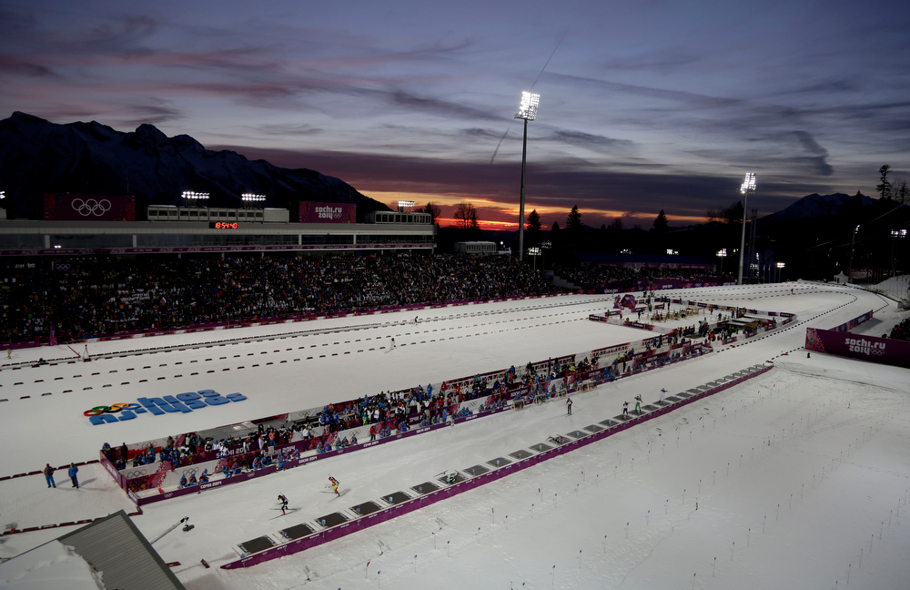 . Skiers compete as the sun sets over the stadium, during the men\'s biathlon 20k individual race, at the 2014 Winter Olympics, Thursday, Feb. 13, 2014, in Krasnaya Polyana, Russia. (AP Photo/Felipe Dana)