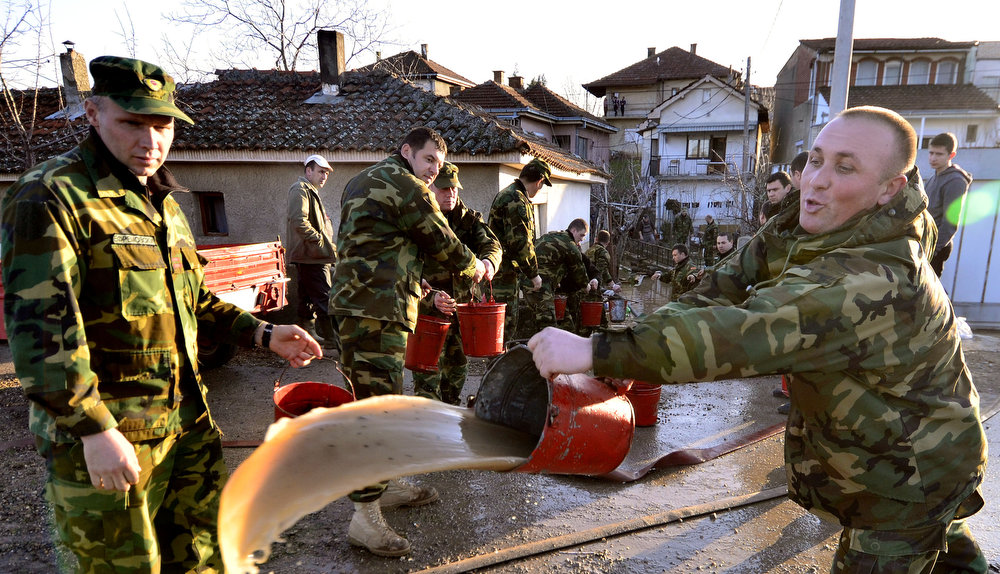 Description of . Macedonian Army soldiers draw water with buckets from the yard of a flooded house in Sveti Nikole, central Macedonia, Tuesday, Feb. 26, 2013. Three days of heavy rain have flooded hundreds of homes in eastern and central Macedonia, destroyed at least two bridges and cut off dozens of villages, causing power cuts and shortages of drinking water. (AP Photo/Boris Grdanoski)