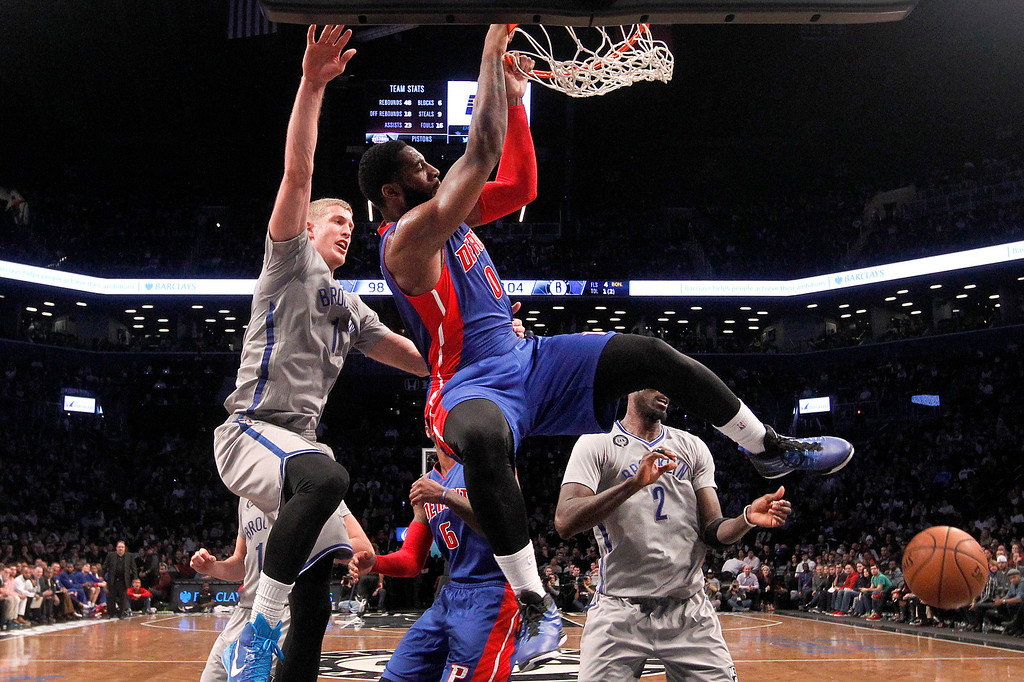 . Detroit Pistons\' Andre Drummond (0) dunks ahead of Brooklyn Nets\' Mason Plumlee (1) during the third quarter of an NBA basketball game Sunday, Dec. 21, 2014, in New York.  Brooklyn beat Detroit 110-105. (AP Photo/Jason DeCrow)