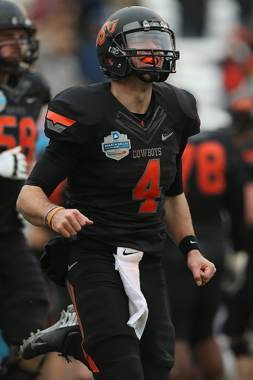 . J.W. Walsh #4 of the Oklahoma State Cowboys celebrates a touchdown against the Purdue Boilermakers during the Heart of Dallas Bowl at Cotton Bowl on January 1, 2013 in Dallas, Texas.  (Photo by Ronald Martinez/Getty Images)