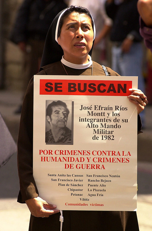 """. A nun carries a poster with a photo of Guatemalan dictator Efrain Rios Montt which reads \""""WANTED: Jose Efrain Rios Montt and those associated with his High Military Order of 1982. For war crimes and crimes against humanity\"""" in front of the public ministry in Guatemala City, Guatemala, Wednesday, June 6, 2001. Residents of 11 villages hit by army massacres in the early 1980s filed a genocide complaint with prosecutors against former Guatemalan dictator Efrain Rios Montt.  (AP Photo/Jaime Puebla)"""