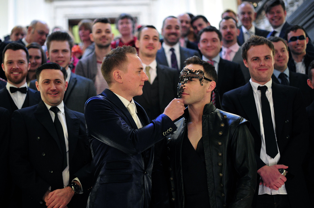 """. Tim Jarmaine-Groves (L) adjusts the face mask of his husband Richard Jarmaine-Groves after their same-sex wedding in north London on March 29, 2014.  Gay couples across England and Wales said \""""I do\""""  as a law authorizing same-sex marriage came into effect at midnight, the final stage in a long fight for equality.  (CARL COURT/AFP/Getty Images)"""