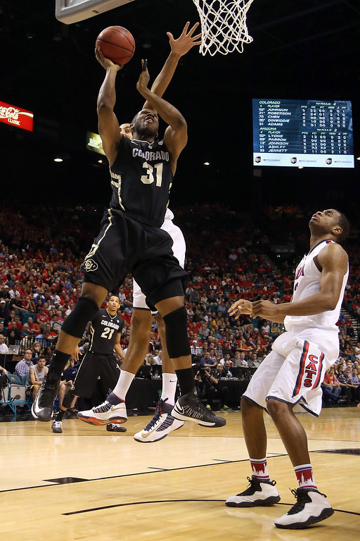 . Jeremy Adams #31 of the Colorado Buffaloes goes up for a shot as Kevin Parrom #3 of the Arizona Wildcats looks up in the first half during the quarterfinals of the Pac-12 tournament at the MGM Grand Garden Arena on March 14, 2013 in Las Vegas, Nevada.  (Photo by Jeff Gross/Getty Images)