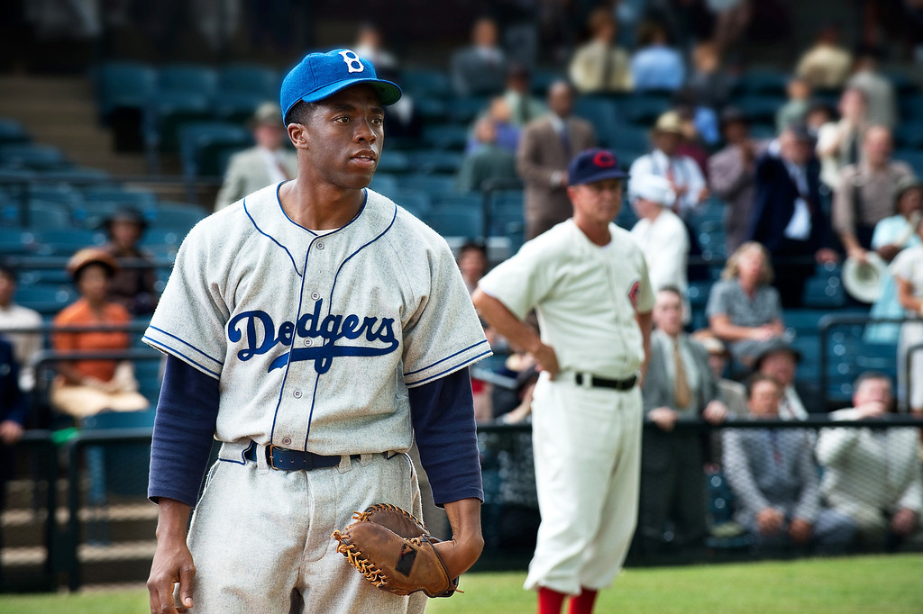 ". This film image released by Warner Bros. Pictures shows Chadwick Boseman as Jackie Robinson in a scene from ""42.\"" Kansas City\'s Negro Leagues Baseball Museum is hosting an advance screening of an upcoming movie about Jackie Robinson, who broke major league baseball\'s color barrier. Thomas Butch of the financial firm Waddell and Reed announced Wednesday, March 20, 2013, that actors Harrison Ford and Andre Holland will be among those appearing at an April 11 screening of \""42.\""  The film chronicles Robinson\'s rise from the Negro Leagues\' Kansas City Monarchs in 1945 to the Brooklyn Dodgers in 1947, when he won the inaugural Rookie of the Year award. The film opens nationwide on April 12. (AP Photo/Warner Bros. Pictures, D. Stevens)"