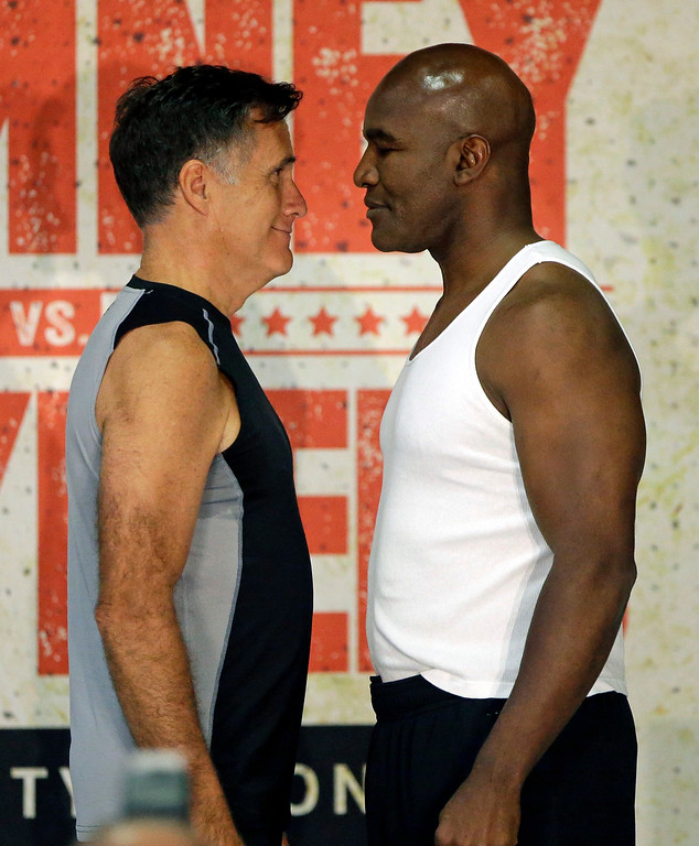 . In this Thursday, May 14, 2015, photo, former Republican presidential candidate Mitt Romney, left, and five-time heavyweight boxing champion Evander Holyfield face each other during an official weigh-in, in Holladay, Utah. Romney and Holyfield are set to square off at a charity fight on Friday, May 15, in Salt Lake City. The black-tie event will raise money for the Utah-based organization CharityVision, which helps doctors in developing countries perform surgeries to restore vision in people with curable blindness. (AP Photo/Rick Bowmer)