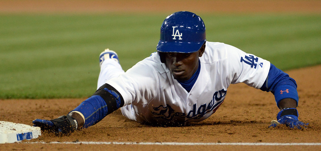 . Los Angeles Dodgers\' Dee Gordon dives back to first base on a pick-off attempt by the Philadelphia Phillies in the second inning of a baseball game on Tuesday, April 22, 2013 in Los Angeles.   (Keith Birmingham/Pasadena Star-News)