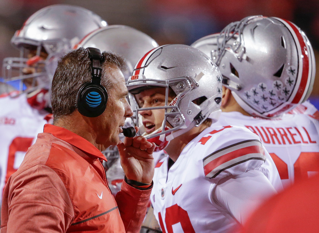 . Ohio State head coach Urban Meyer talks to on his headset as quarterback Joe Burrow (10) talks to a different person, during a time out in the second half of an NCAA college football game against Nebraska in Lincoln, Neb., Saturday, Oct. 14, 2017. Ohio State won 56-14. (AP Photo/Nati Harnik)