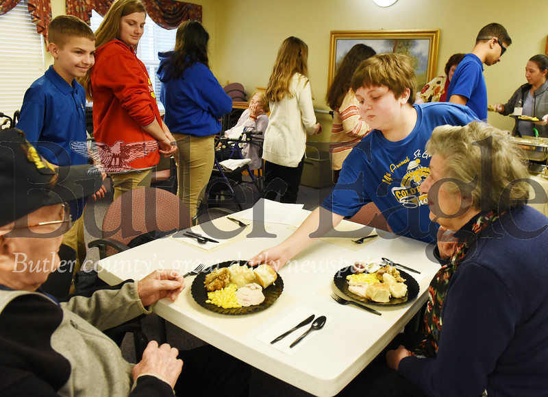 Harold Aughton/Butler Eagle: Camten Fazzino, 14, of St. Gregory's serves turkey dinners to Andrew Szakelyhizi, 97, and his wife, Stella, 92, at the Newhaven Court, Tues., Nov. 19, 2019. The Szakelyhizi have been married for 69 years.