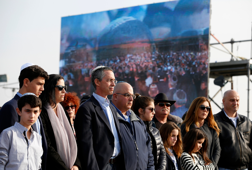 . The sons of former Israeli Prime Minister Ariel Sharon, Gilad, 4th left, and Omri, 5th left, attend their father\'s funeral near Sycamore Farm, Sharon\'s residence in southern Israel, Monday, Jan. 13, 2014. Sharon was laid to rest Monday at his ranch in southern Israel as the nation bid a final farewell to one of its most colorful and influential leaders- a man venerated by supporters as a warrior and statesman but reviled in the Arab world as a war criminal.(AP Photo/Baz Ratner, Pool)