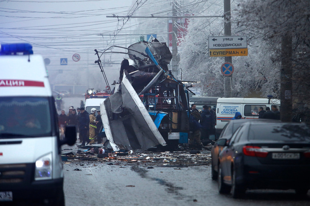 . Experts and police officers examine a site of a trolleybus explosion in Volgograd, Russia Monday, Dec. 30, 2013. A bomb blast tore through the trolleybus in the city of Volgograd on Monday morning, killing at least 14 people a day after a suicide bombing that killed at 17 at the city\'s main railway station. (AP Photo/Denis Tyrin)