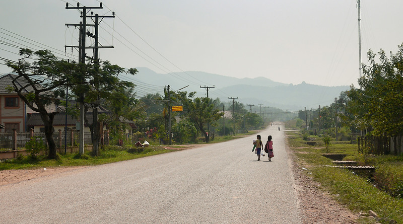 Two young little girls walk side-by-side home from school in rural Laos.