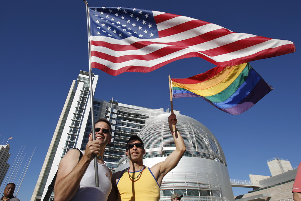 . Johnny Zych and Terry Vargas, from left, wave flags at City Hall to celebrate the Supreme Court decision on Prop. 8 and gay marriage in San Jose, Calif., on Wednesday, June 26, 2013. (LiPo Ching/Bay Area News Group)