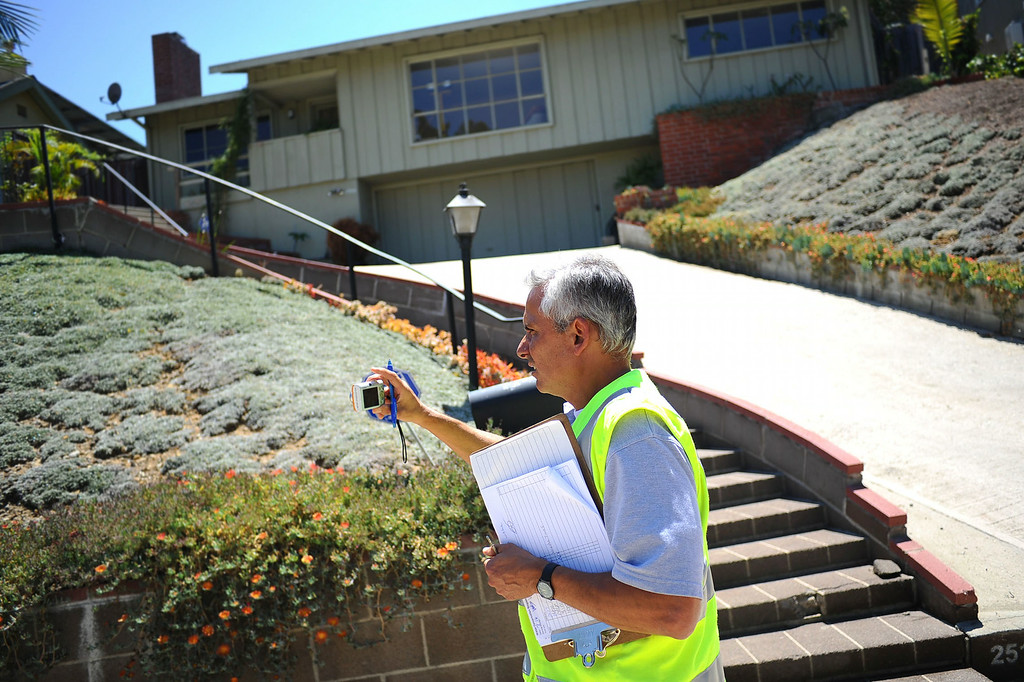 . Rick Silva of the DWP�s Water Conservation Response Unit documents a water ordinance violation while on patrol in the Sliver Lake area Wednesday July 17, 2014.  Silva is in charge of monitoring water violations in LADWP\'s service area of just under 500 square miles. (Andy Holzman/Los Angeles Daily News)