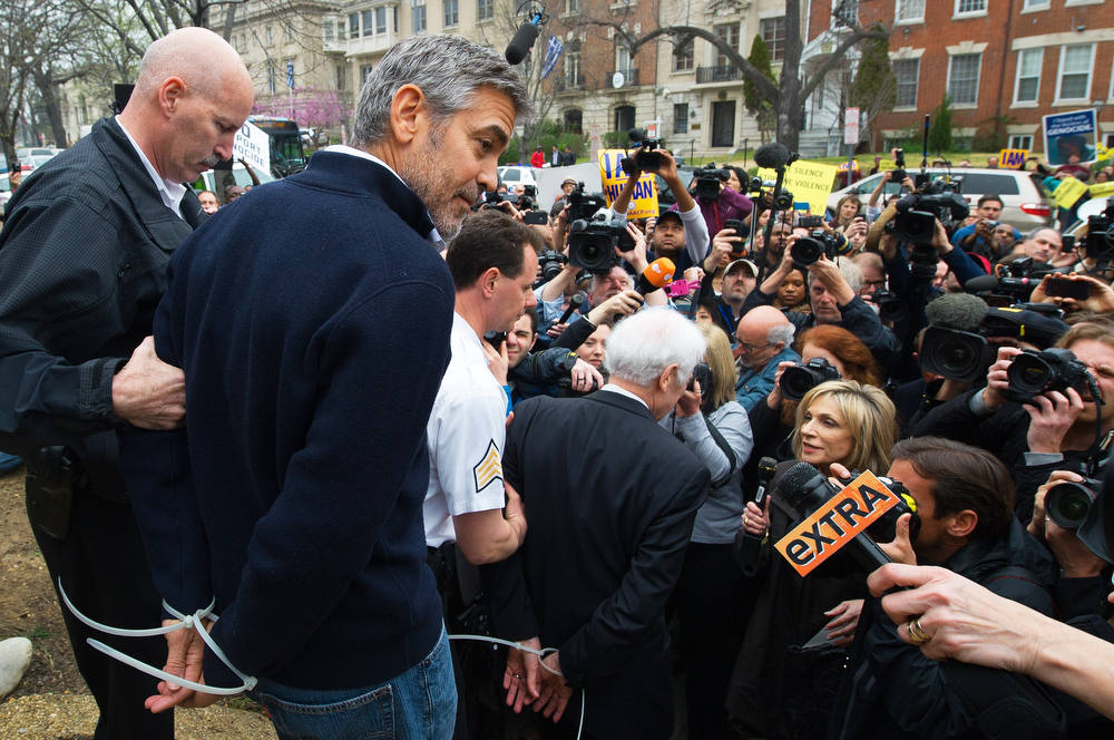 Description of . Actor and activist George Clooney (2nd L) and his father journalist Nick Clooney (C) are arrested for trespassing upon the Sudanese Embassy in Washington, DC, on March 16, 2012. Clooney and his father were protesting against human rights abuses by the Sudanese government.       AFP PHOTO/PAUL J.  RICHARDS/AFP/Getty Images
