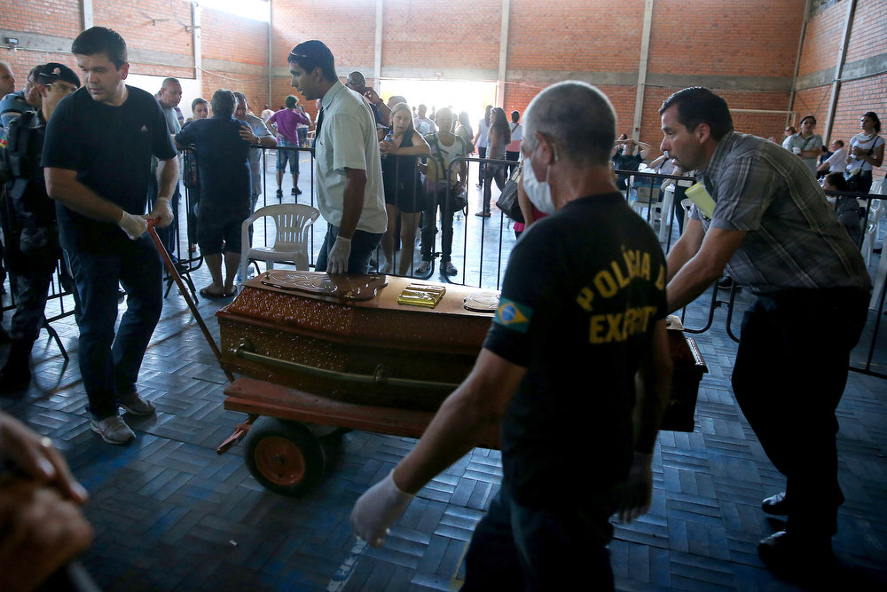 Description of . Relatives of a victim killed in the Kiss nightclub blaze carry his coffin at the municipal gymnasium on January on January 28, 2013 in Santa Maria, southern Brazil. Brazilians were mourning the victims of a nightclub blaze in a small college town that left more than 230 people dead and over 100 injured, with many still fighting for their lives. AFP PHOTO / JEFFERSON BERNARDES