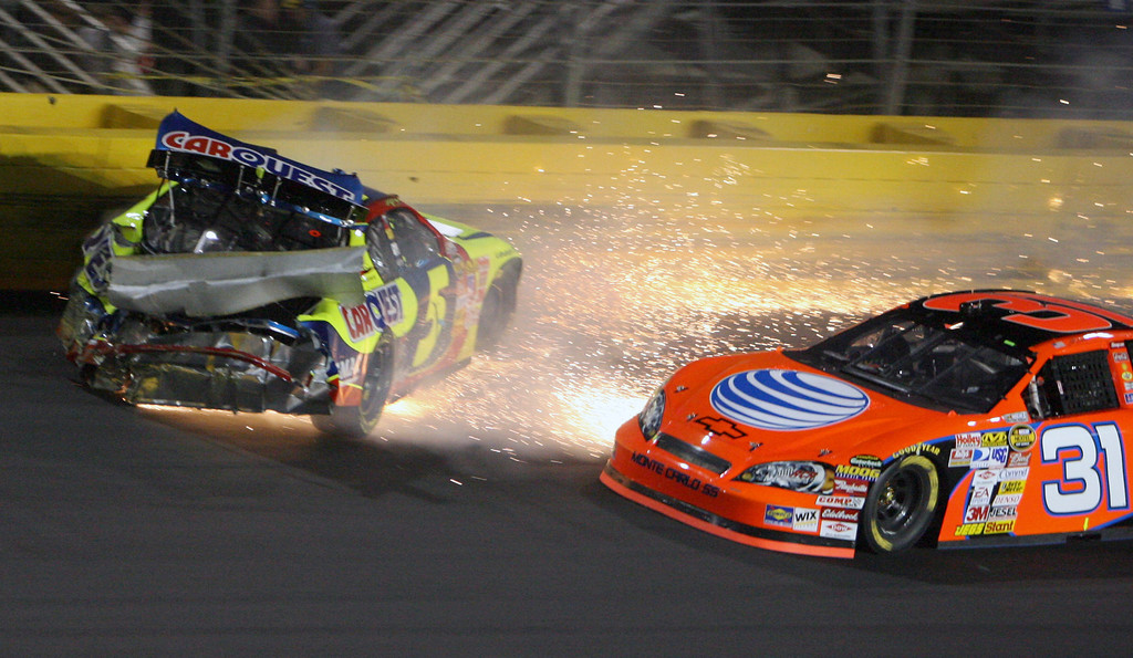 . Kyle Busch, left, crashes as Jeff Burton, right, drives past during the NASCAR Nextel All-Star Challenge auto race at Lowe\'s Motor Speedway in Concord, N.C., Saturday, May 19, 2007. (AP Photo/Ron Fischer)