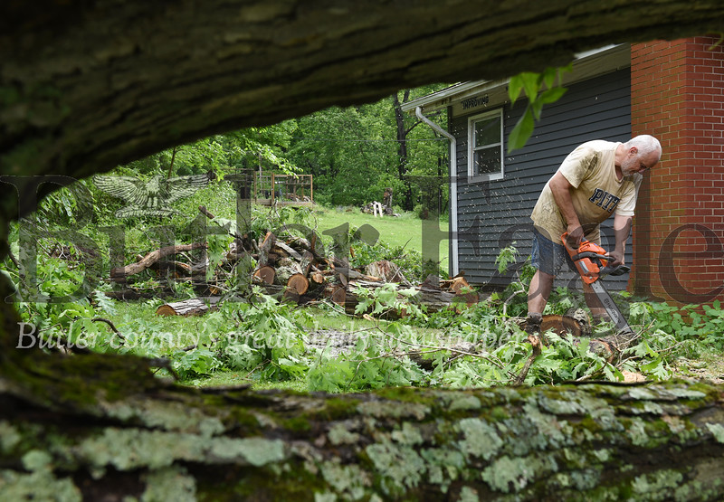 Harold Aughton/Butler Eagle: Larry Matko of 153 Cashdollar Road, cuts up a a limb from a nearly 60 ft. tree that landed on the roof of his house, Wednesday, May 29.