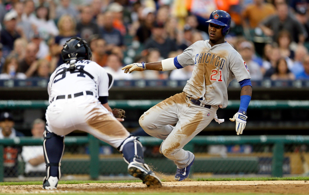 . Detroit Tigers catcher James McCann prepares to tag out Chicago Cubs\' Junior Lake as Lake attempted to score from second on a single by Addison Russell during the fifth inning of a baseball game, Tuesday, June 9, 2015, in Detroit. (AP Photo/Carlos Osorio)
