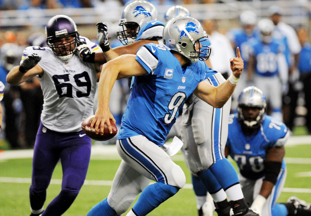 . Lions quarterback Matthew Stafford scrambles right while pursued by Vikings defensive end Jared Allen, left, who is blocked in the second quarter.  (Pioneer Press: Chris Polydoroff)