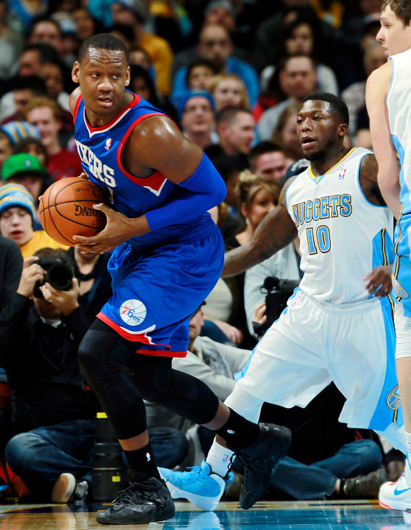 . Philadelphia 76ers center Lavoy Allen, left, picks up a loose ball as Denver Nuggets guard Nate Robinson covers in the fourth quarter of the Sixers\' 114-102 victory in an NBA basketball game in Denver on Wednesday, Jan. 1, 2014. (AP Photo/David Zalubowski)