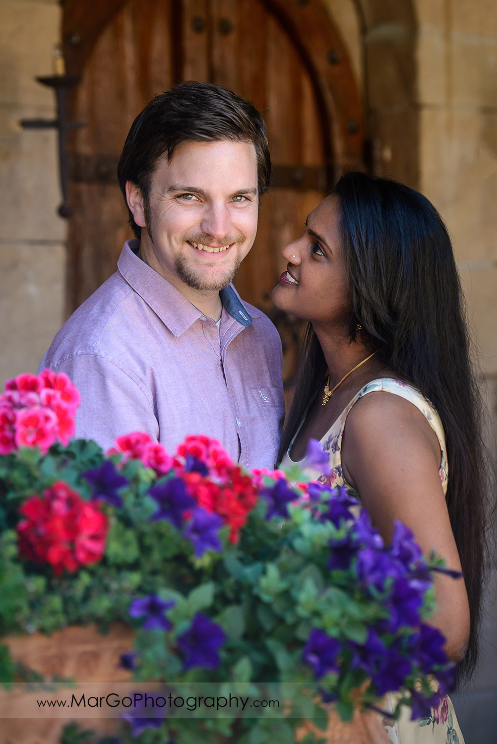 portrait of Indian woman in flower dress looking at man in pink shirt looking into camera during engagement session at Castello di Amorosa in Calistoga