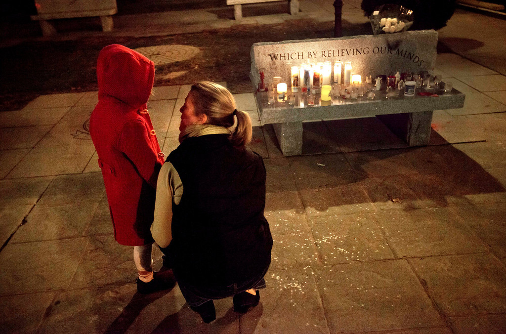 . Rhonda Eleish, right, talks to her daughter Kari Ergmann, 6, both of Bridgewater, Conn., next to a candlelight vigil outside the Edmond Town Hall, Saturday, Dec. 15, 2012, in Newtown, Conn. Eleish suspects her daughter knew one of the victims of Friday\'s shooting at Sandy Hook Elementary School in Newtown that killed 26 people, including 20 children. (AP Photo/David Goldman)
