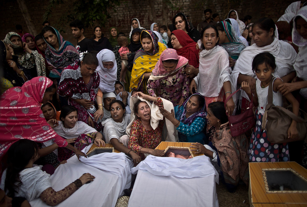 . Pakistani women grieve over the coffins of their relatives, who were killed in a suicide attack on a church, in Peshawar, Pakistan, Sunday, Sept. 22, 2013.  (AP Photo/Muhammed Muheisen)