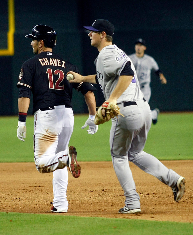 . Colorado Rockies second baseman DJ LeMahieu, right, tags out Arizona Diamondbacks Eric Chavez, left, in the fifth inning during a baseball game on Sunday, July 7, 2013, in Phoenix. (AP Photo/Rick Scuteri)