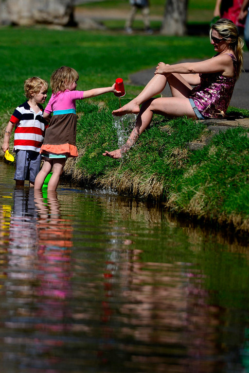 . Lisa Wargo receives a Mothers\' Day foot cleaning from her daughter, Skylar, and her son, Ty, in Smith\'s Ditch at Washington Park. Temperatures reached the low 80s in Denver. (Photo by AAron Ontiveroz/The Denver Post)