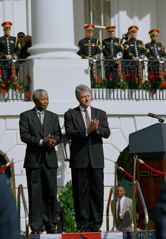 ". President Bill Clinton and South African President Nelson Mandela applaud during a  ceremony for the South African president on Tuesday, Oct. 4, 1994 on the occasion of his official visit at the White House.   President Clinton welcomed President Mandela saying the South African leader\'s path from imprisonment in an apartheid state to the presidency of a new democracy is ""proof that the human spirit can never be crushed.\""  (AP Photo/Dennis Cook)"