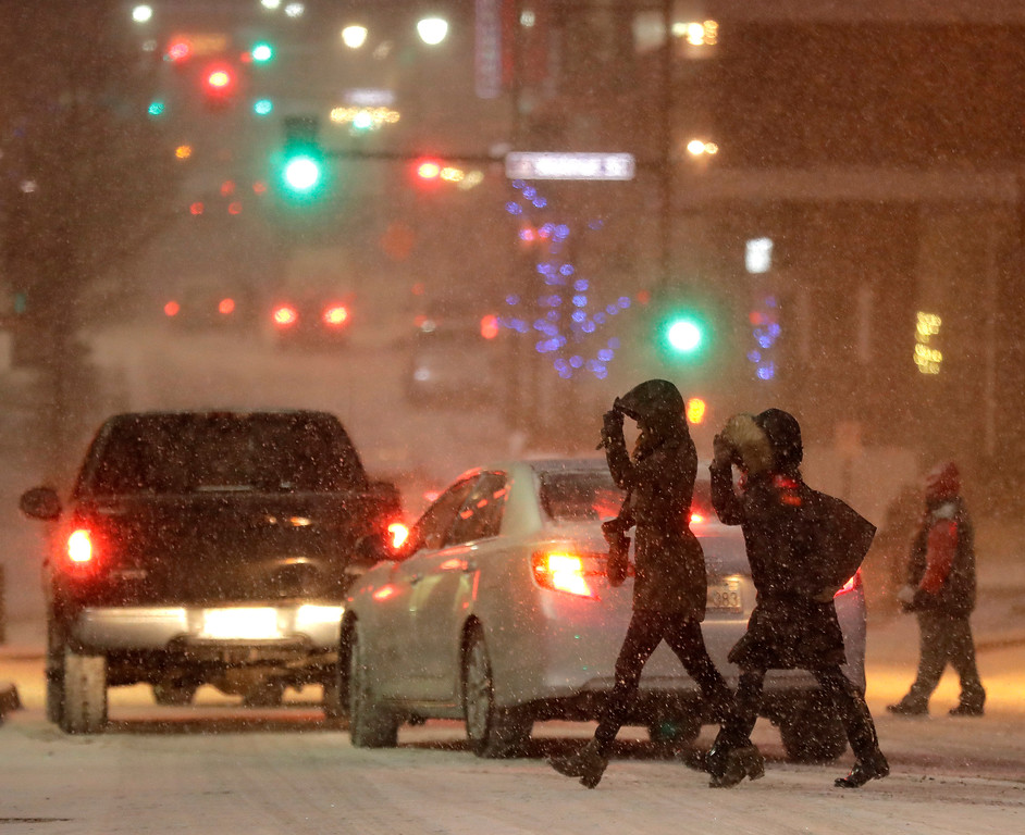 . Pedestrians walk across a snowy street in downtown Kansas City, Mo., on Saturday, Dec. 17, 2016. A winter storm of snow, freezing rain and bone-chilling temperatures hit the nation\'s mid-section and East Coast on Saturday. (AP Photo/Charlie Riedel)