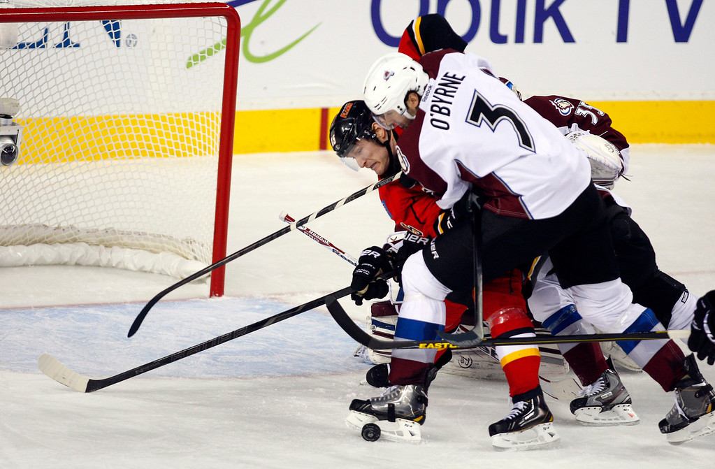 . Colorado Avalanche\'s Ryan O\'Byrne, right, competes with Calgary Flames\' Tim Jackman for the puck in front of the Avalanche net during the second period of an NHL hockey game Thursday, Jan. 31, 2013, in Calgary, Alberta. (AP Photo/The Canadian Press, Jeff McIntosh)