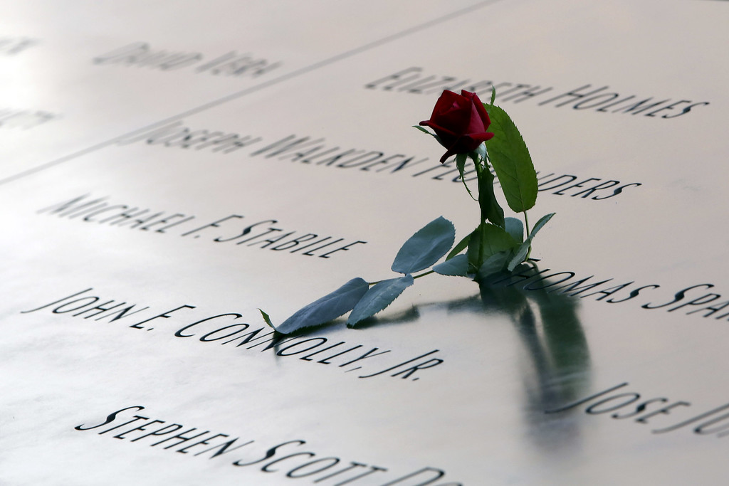 . A rose is left by the names engraved in the South Pool of the 9/11 Memorial during ceremonies for the twelfth anniversary of the terrorist attacks on lower Manhattan at the World Trade Center site on September 11, 2013 in New York City.  (Photo by Mary Altaffer-Pool/Getty Images)
