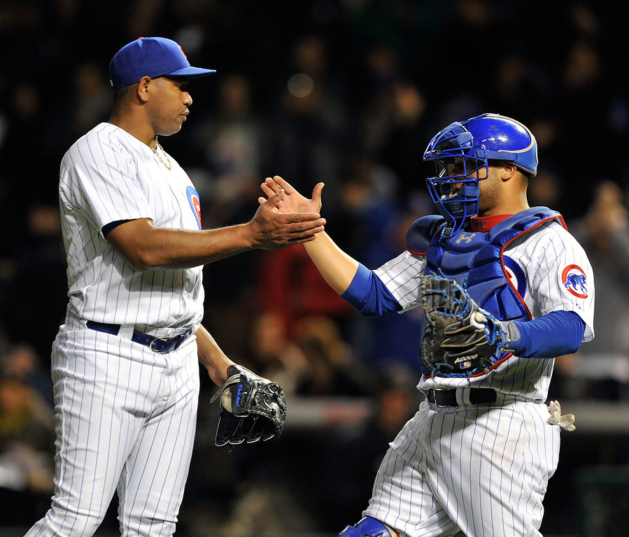 . Chicago Cubs\' Carlos Marmol left, and Welington Castillo celebrate the Cubs 9-1 victory over the Colorado Rockies after a baseball game Monday, May 13, 2013, in Chicago. (AP Photo/Jim Prisching)