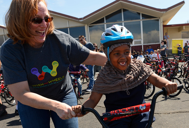 . Cindy Tayler, a volunteer for Wish for Wheels, helps six-year-old Bahsan Aweys ride her new bike at Sable Elementary in Aurora, May 14, 2013. This was the first time Bahsan had ever been on a bike. Panera Bread and Wish for Wheels, a local non-profit, donated 140 new bikes to benefit area kindergarteners around Denver. (Photo By RJ Sangosti/The Denver Post)