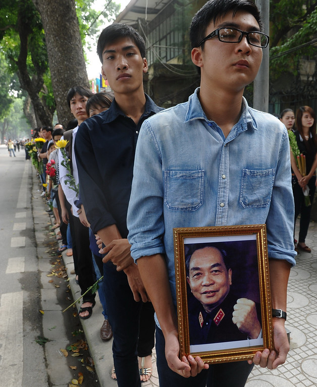 . A man holds a portrait of late General Vo Nguyen Giap as he lines up among thousands of others outside the residence of late General Vo Nguyen Giap before entering to pay homage to the national independence hero in Hanoi on October 6, 2013. Vietnam announced plans to hold a national funeral for independence hero General Vo Nguyen Giap in the first official statement on the death of the ruthless but brilliant military strategist. HOANG DINH NAM/AFP/Getty Images