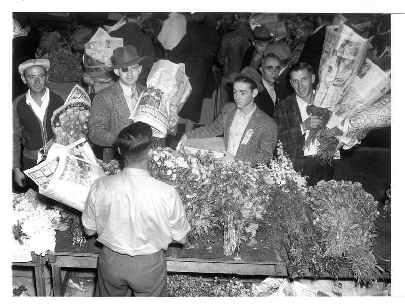 """""""Florists purchasing flowers in the Japanese wholesale flower market in Los Angeles.  The cultivation and sale of flowers attracts a good many West Coast Japanese.""""--caption on photograph"""